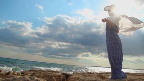 Strong woman standing on sea rocks, enjoying freedom, feeling of female dignity. Stock footage stock video footage