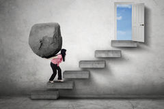 Strong woman with stone on stairs. Picture of a strong businesswoman brings a big stone on her back while climbing a stairs toward a doorway Stock Images