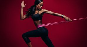 Strong woman using a resistance band in her exercise routine. Strong women using a resistance band in her exercise routine. Female athlete exercising with Stock Image