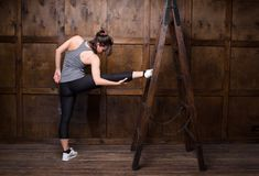 Strong woman using a wooden ladder Royalty Free Stock Images