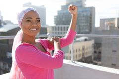 Strong woman in city with breast cancer awareness. Strong woman wearing mantra scarf in the city with breast cancer awareness royalty free stock photo