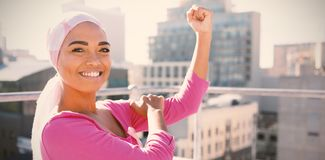 Strong woman in city with breast cancer awareness stock photography