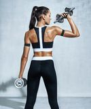 Strong woman working out with dumbbells, flexing her arm Royalty Free Stock Image