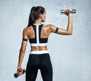 Strong woman working out with dumbbells, flexing her arm. Stock Photo
