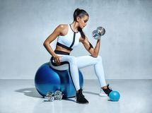 Strong woman working out with dumbbells sitting on gymnastic ball. Photo of sporty latin woman in sportswear on grey background. Sports Royalty Free Stock Images