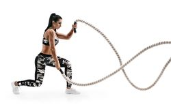 Strong woman workout with battle ropes. Photo of latin woman in military sportswear isolated on white background. Strength and motivation. Side view stock photo