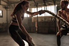 Strong woman workout with battle ropes. Strong women workout with battle ropes at the gym with personal trainer. Battle rope workout at gym with instructor Royalty Free Stock Photo