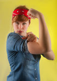 Strong woman after WW2 poster rosie the riveter. Strong redhead woman showing her biceps wearing a blue jeans shirt and red ribbon in her red hair as in the `yes royalty free stock photos