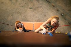Strong woman and business concept. Top view of two young climbers approaching to finishing point on the speed track of Stock Photo