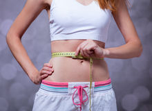 Strong women's abs. Beautiful and strong women's abs with metre. Studio shot royalty free stock photos