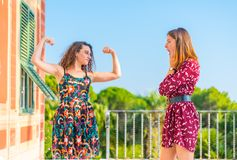 Strong women showing physical strength. Strong young women showing her muscles and physical strength. Girl power, girls are independent and powerful royalty free stock image