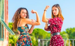 Strong women showing physical strength. Strong young women showing her muscles and physical strength. Girl power, girls are independent and powerful royalty free stock photography