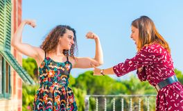 Strong women showing physical strength. Strong young women showing her muscles and physical strength. Girl power, girls are independent and powerful stock photo