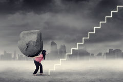 Strong worker with boulder climbs stairs Royalty Free Stock Image