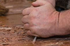 Strong working hands doing repairs. In the hands of a screwdriver. We rip off the paint off the floor Stock Image