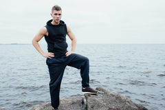 Strong yang fitness man poses on beach near sea and rocks. royalty free stock images