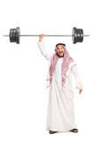 Strong young Arab lifting a heavy barbell Royalty Free Stock Image