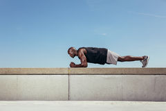 Strong young athlete doing core exercise. Side view of strong young african athlete doing core exercise on a wall by a walkway. Muscular young athlete exercising royalty free stock images