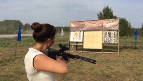 Strong young beautiful woman standing in a field in the dash and aim a crossbow at a target,. 1920x1080 stock video footage