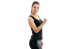 Strong young brunette sport girl in black unform. Looking at the camera isolated on white background Royalty Free Stock Photos