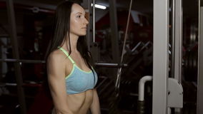 Strong young brunette woman training in sport gym. Beautiful girl with long dark hair doing exercises on modern professional sport equipment in gym stock footage