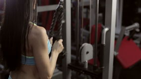 Strong young brunette woman training in sport gym. Beautiful girl with long dark hair doing exercises on modern professional sport equipment in gym stock video footage