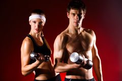 Strong young couple working out with dumbbells. Shot in studio on a red background stock photos