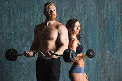 Strong young couple working out with dumbbells. Stock Photos