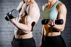 Strong young couple working out with dumbbells. Shot in studio on a white background royalty free stock photography