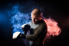 Athlete posing against smoke. A strong young dark-haired male athlete in a green sports jacket posing and wearing black and white boxing gloves against a royalty free stock photography