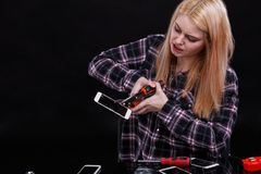 A strong young girl pinches a smartphone with a broken screen. Black background. stock photography