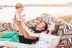 Free Strong Young Father Holding His Baby Daughter In Hands With Happy Hipster Mother, Smiling Family Relaxing In A Hammock On A Beach Royalty Free Stock Image - 167249516