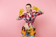 Strong young fun handyman woman in plaid shirt, denim shorts, yellow gloves, kit tools belt full of variety useful. Instruments isolated on pink background royalty free stock images