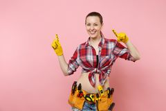 Strong young fun handyman woman in plaid shirt, denim shorts, yellow gloves, kit tools belt full of variety useful. Instruments isolated on pink background stock photography