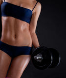 Strong young girl working out with dumbbells. Stock Photo