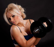 Strong young girl working out with dumbbells. Royalty Free Stock Photo