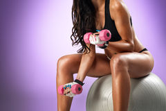 Strong young. Girl working out with dumbbells stock image