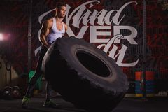 A guy throws a huge heavy wheel. Indoors in the gym. Strong young guy brunette, European appearance, throws a huge heavy wheel. Indoors in the gym Royalty Free Stock Images