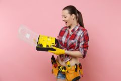 Strong young handyman woman in plaid shirt, denim shorts, kit tools belt full of different instruments holding toolbox. Isolated on pink background. Female in royalty free stock photo