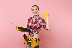 Strong young handyman woman in plaid shirt, denim shorts, kit tools belt full of different instruments holding toolbox. Isolated on pink background. Female in royalty free stock image