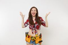 Strong young handyman woman in plaid top shirt, denim shorts, kit tools belt full of variety useful instruments isolated. On white background. Female doing male royalty free stock images