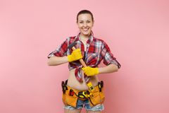 Strong young handyman woman wearing plaid shirt, denim shorts, kit tools belt full of different instruments hammer. Isolated on pink background. Female in male royalty free stock photography