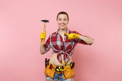 Strong young handyman woman wearing plaid shirt, denim shorts, kit tools belt full of different instruments hammer. Isolated on pink background. Female in male royalty free stock image