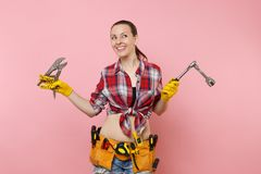 Strong young handyman woman wearing plaid shirt, denim shorts, kit tools belt full of different instruments spanner. Isolated on pink background. Female in male stock photos