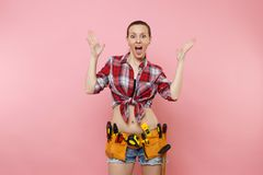 Strong young handyman woman wearing plaid shirt, denim shorts, kit tools belt full of variety useful instruments. Isolated on pink background. Female doing male royalty free stock images
