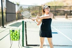 Tennis player warming up on court. Strong young latin woman holding tennis racket stretching her arms before training on tennis court Royalty Free Stock Photos