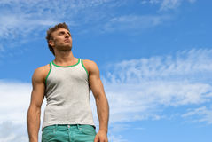 Strong young man on blue sky background. Portrait of a strong young man on blue sky background stock image