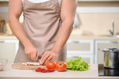 Strong young man chops vegetables in kitchen Royalty Free Stock Photos