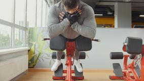 Strong young man doing exercising in workout room. Strong young men doing exercising in workout room, telephoto shot Royalty Free Stock Images