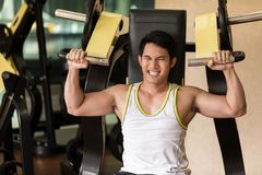 Strong young man exercising for arms muscles at a fitness club. Portrait of a handsome and strong young man smiling while exercising for arms muscles during Stock Photo
